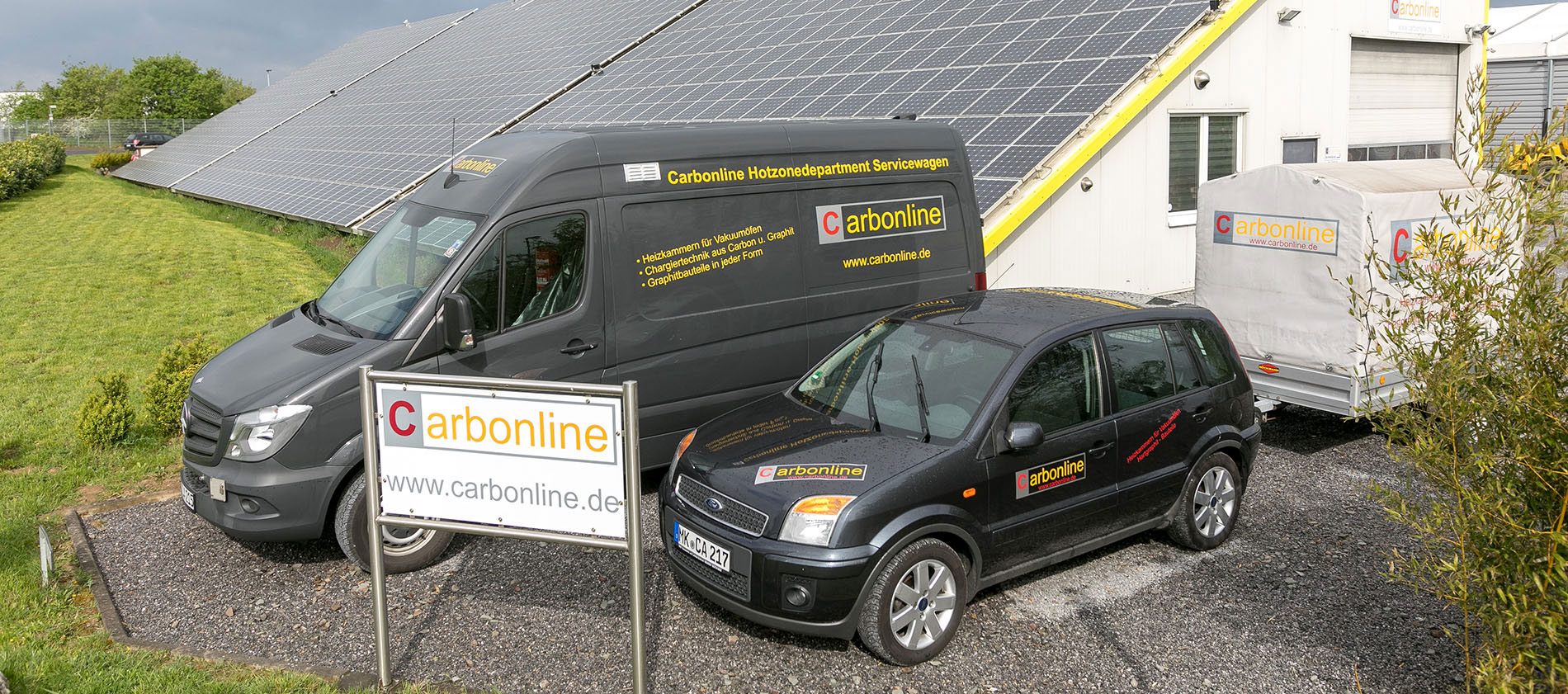 Carbonline Auto und Transporter vor Haus